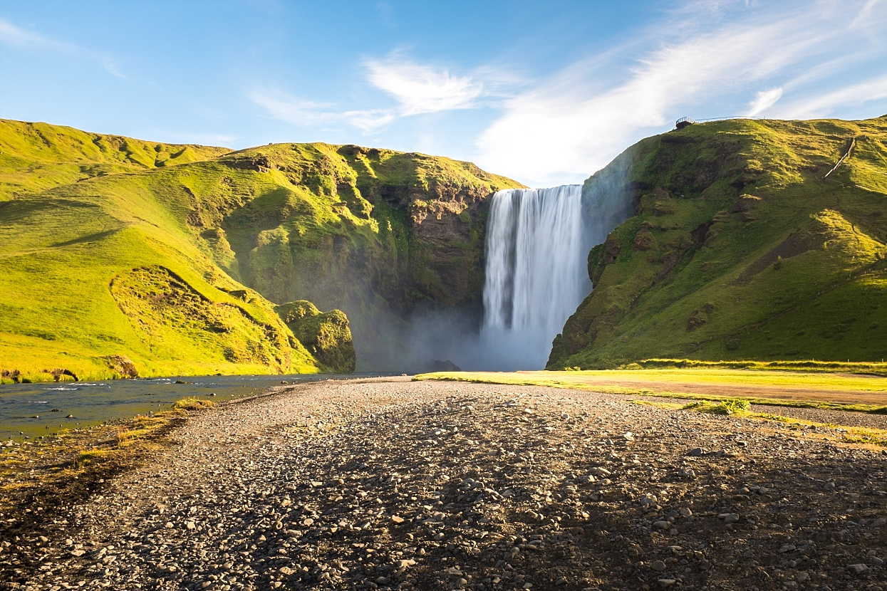 The Skógafoss is one of the biggest waterfalls in the country with a width of 25 metres (82 feet) and a drop of 60 m (200 ft). Due to the amount of spray the waterfall consistently produces, a single or double rainbow is normally visible on sunny days. According to legend, the first Viking settler in the area, Þrasi Þórólfsson, buried a treasure in a cave behind the waterfall. The legend continues that locals found the chest years later, but were only able to grasp the ring on the side of the chest before it disappeared again. The ring was allegedly given to the local church. The old church door ring is now in a museum, though whether it gives any credence to the folklore is debatable